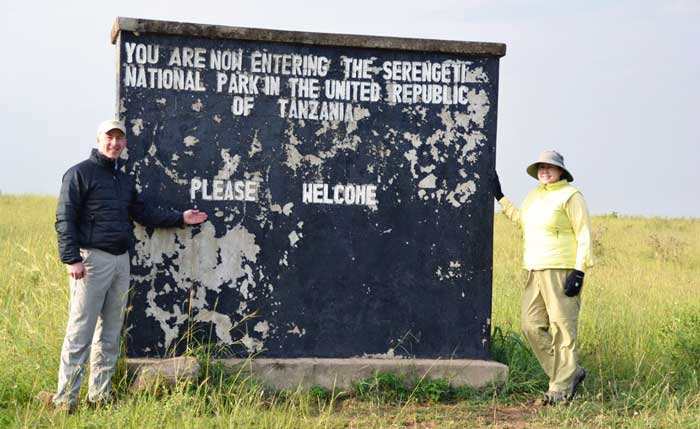 Danielle and husband with sign in Tanzania
