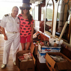 Sarah with a crew member and boxes of supplies