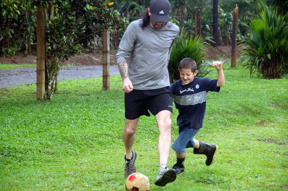 John's son playing soccer with the schoolchildren